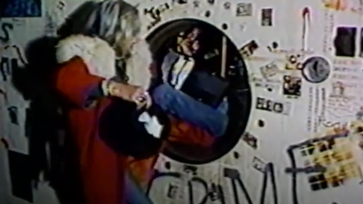 Woman climbs through a hole into a graffiti'd beer tank