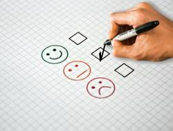 Picture of someone filling out survey with three options: smiley face, neutral face, unhappy face