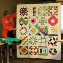 "A bright quilt composed of ""block of the month"" blocks."