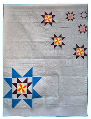 quilt with large star in lower left corner and smaller stars in upper right corner