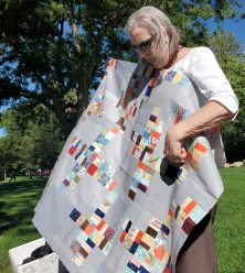 woman holding up a gray and multicolor quilt