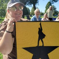 woman holding small quilt with Hamilton Musical logo