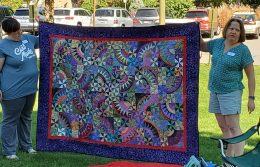 women holding up quilt