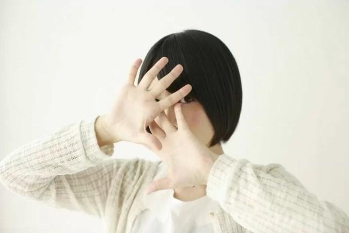 顔を隠す人