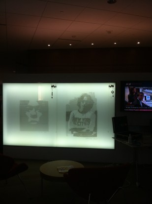 Drawings of John Lennon and Miles Davis on illuminated glass.