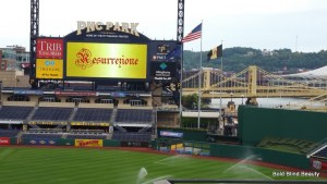 Picture of the scoreboard with the logo on it on the far side of the baseball diamond.