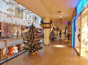 Upper level of a empty mall with Christmas Trees and curtains of lights and stars hanging from the ceiling.