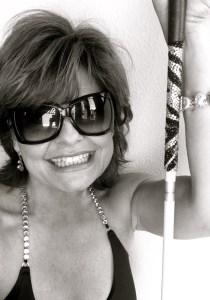 Photo of Kimberly holding her bejeweled White cane