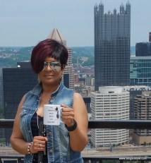 "I'm standing on the platform overlooking Pittsburgh holding a mug that says ""My Friend Is Bold Blind & Beautiful"". In the background is PPG Place sometimes referred to as the glass castle."