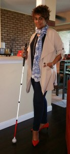 I'm posing in a standing position facing the camera with my white cane in my right hand.