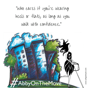 """Who cares if you're wearing heels or flats, as long as you walk with confidence."" Image: A whimsical image of a blue cityscape with Abigail walking past and the hashtag #AbbyOnTheMove on the bottom."