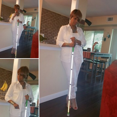 I'm posting with my white cane in front of my counter. I'm wearing white jeans, a white cami under a white shirt with the sleeves rolled up. My shoes are tan laced-up sandals with stacked heels and my accessories are a silver bracelet and statement necklace.