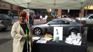 Steph McCoy stands with her with cane in front of Bold Blind Beauty's display at White Cane Safety Day celebration in Pittsburgh's Market Square.