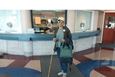 "The header is of a photo of me standing with my gold Ambutech slimline white cane in the Erie Greyhound terminal wearing jeans, olive tee, olive sweater, tan ball cap, light flats, and wooden hoop earrings. I have on my Checkered Eye ""low vision"" pin and am holding an olive backpack and denim jacket. This photo is especially meaningful to me because it was the first time I took a solo bus trip from PA to NY as my best friend was diagnosed with cancer and I had to get to her."