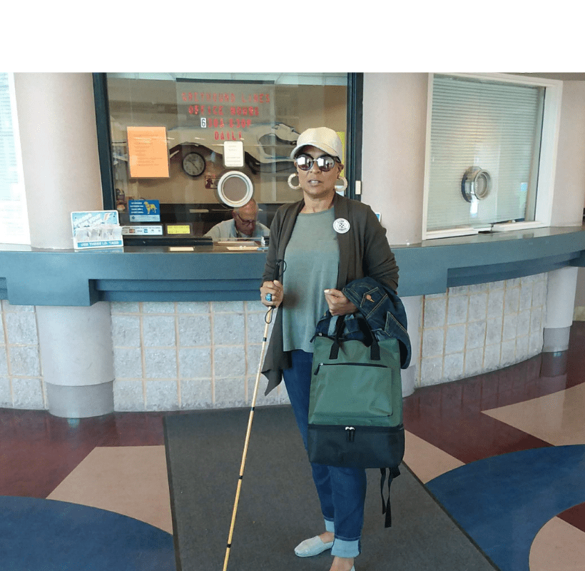 """The header is of a photo of me standing with my gold Ambutech slimlinewhite canein the Erie Greyhound terminal wearing jeans, olive tee, olive sweater, tan ball cap, light flats, and wooden hoop earrings. I have on my Checkered Eye """"low vision"""" pin and am holding an olive backpack and denim jacket. This photo is especially meaningful to me because it was the first time I took a solo bus trip from PA to NY as my best friend was diagnosed with cancer and I had to get to her."""