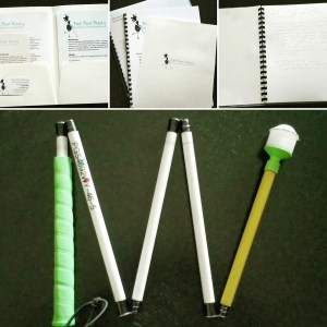 Collage of Bold Blind Beauty informational packets in print, large print and braille. The bottom photo is my Ambutech custom white cane. The grip is neon green, the last section is neon yellow and the rest of the cane is white.