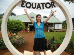 """Virginia is straddling the equator in Uganda. She is standing with arms outstretched in an upright circle that has """"Equator"""" in bold lettering at the top of the circle."""
