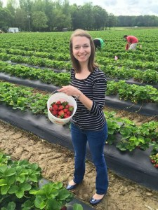 Photo of Virginia at a strawberry picking farm. She is standing in a field of strawberries holding a bucket of the fruit.
