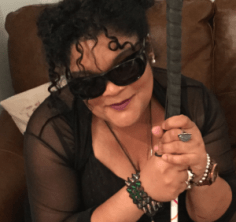 Angela (Angie) Roberts is looking like a rock star in her fabulous oversized shades, a sheer black cover-up over a black flapper dress, and jewelry.