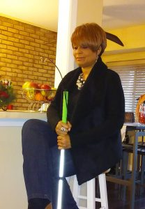 Photo of me sitting on my bar stool with my white cane in hand wearing the outfit described in the post.