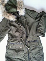 A parka is awesome in cold weather. This one is an olive, fur-trimmed hooded parka with gold accents. Roomy pockets and faux-leather trim around the pockets and zipper/snaps.