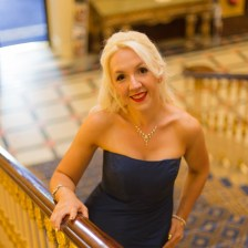 Lizzie is posing on a staircase with her right hand on the railing and left hand on her hip. She is wearing a navy blue strapless gown with a dainty necklace and a bracelet on each wrist.