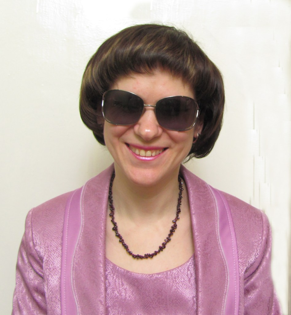Headshot of Oksana Chuchunkova wearing a pink top with matching jacket and complementary lip color. Her brown hair is bob styled and she's wearing a pair of sunglasses.