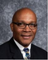 Professional headshot of Robert a bald African American with eyeglasses and wearing a suit and tie.