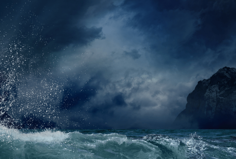 Stormy weather with a big wave and dark rock in the stormy sea