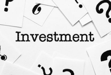 "Header image is black & white. The word ""Investment"" is in the center surrounded by question marks."