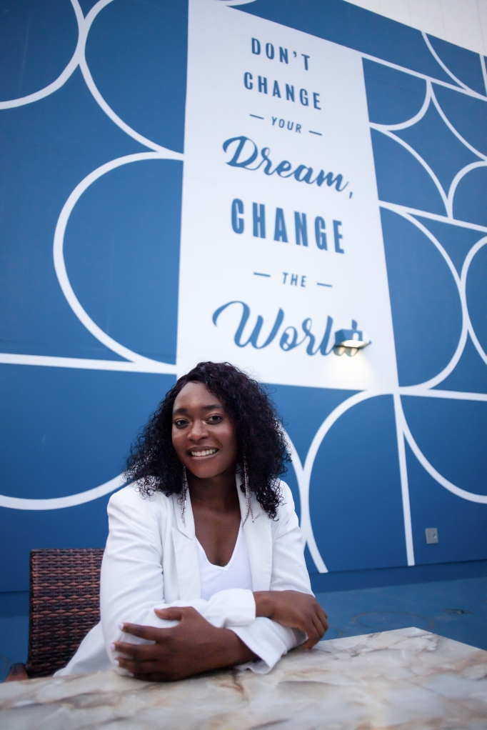 "The full-size header image shows Fatmatta sitting down with curly hair wearing a white jacket and white shirt in front of a blue wall with circle designs with the quote that says ""Don't change your dream change the world."""