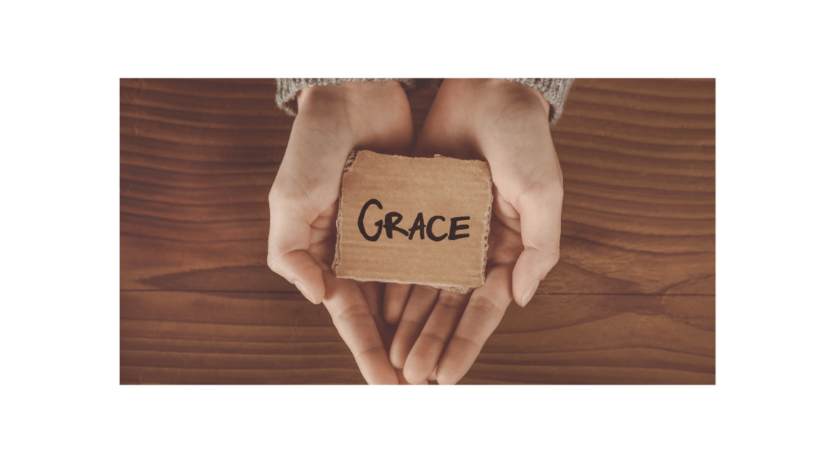 "Two hands holding a piece of cardboard with the word ""grace"" written on it."