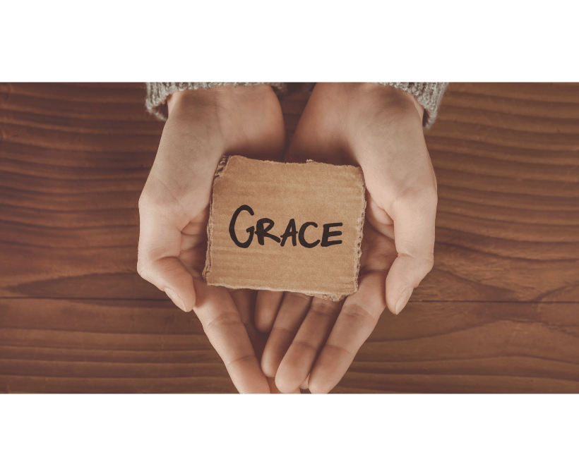 """Two hands holding a piece of cardboard with the word """"grace"""" written on it."""
