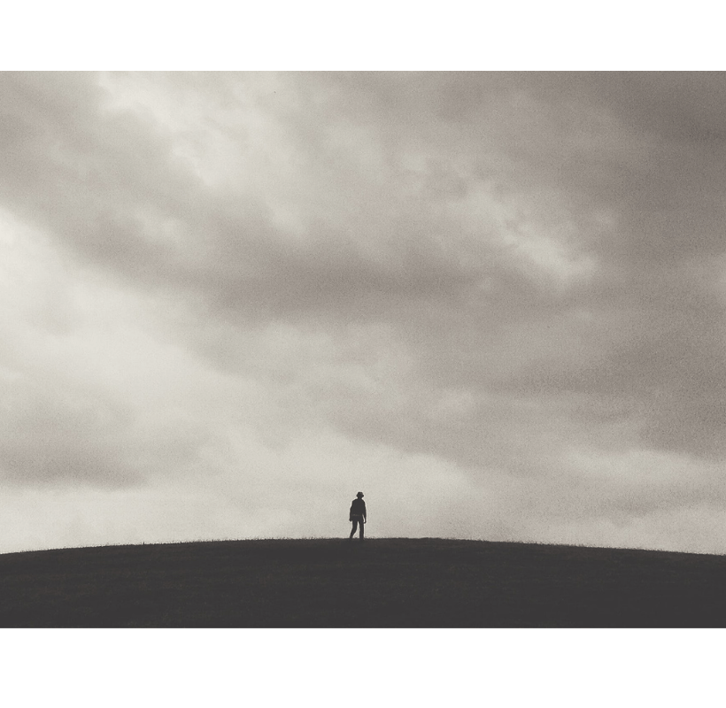 A lone person is standing in an open field under a cloudy sky.
