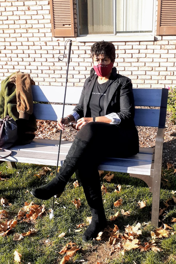 Photo of Steph sitting outside on a bench wearing her red mask, black tee and posing with her black cane.