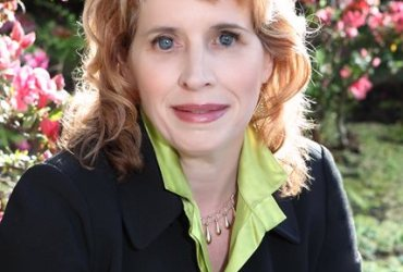 In this outdoor headshot Gena Harper is wearing a black jacket with a light green shirt. A flowing bush is in the background.