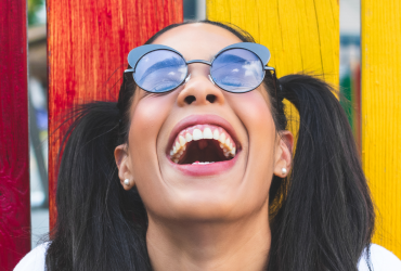 Dark-haired woman in sunglasses is laughing heartily with her head thrown back and eyes closed.