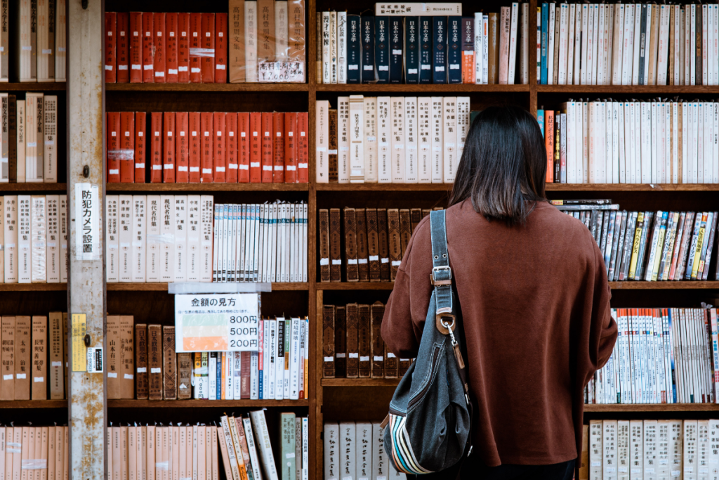 Rear shot of a woman wearing a brown shirt carrying a black leather bag standing in front of library books.