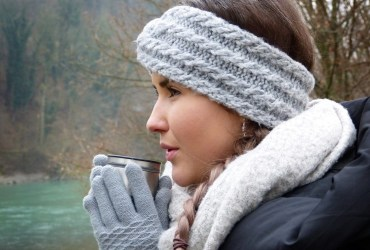 A closeup of a woman outdoors dressed in winter attire (fuzzy headband, gloves, scarf, and winter coat). She is holding a mug close to her mouth.