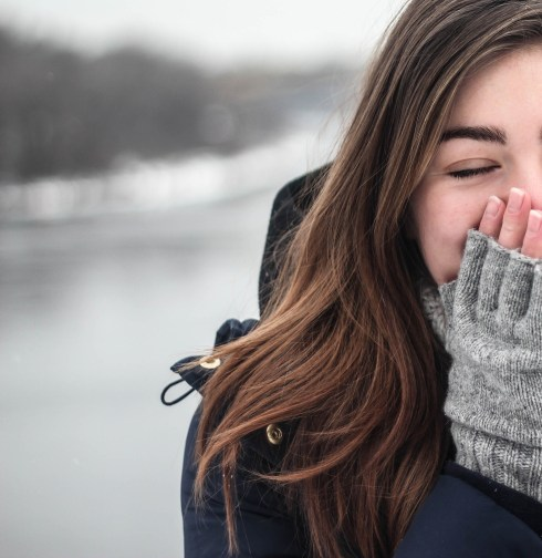 Winter scene closeup of a brunette woman holding her fingerless gloved hands to her face. In the background is snowy scenery.