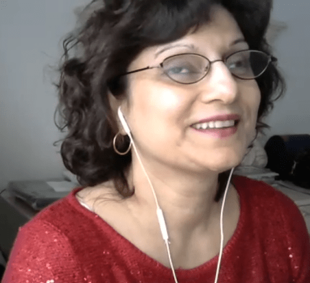 A very clear Zoom photo of a smiling Nasreen who has shoulder length wavy dark hair, wire rimmed glasses and a red sweater.
