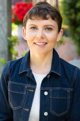 Alicia Connor a pretty brunette with short cropped hair wearing a denim jacket with a white tee.