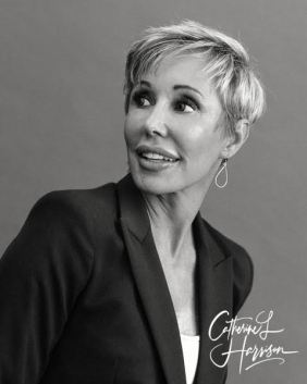 A professional black & white headshot of Catherine Harrison in a suit jacket.