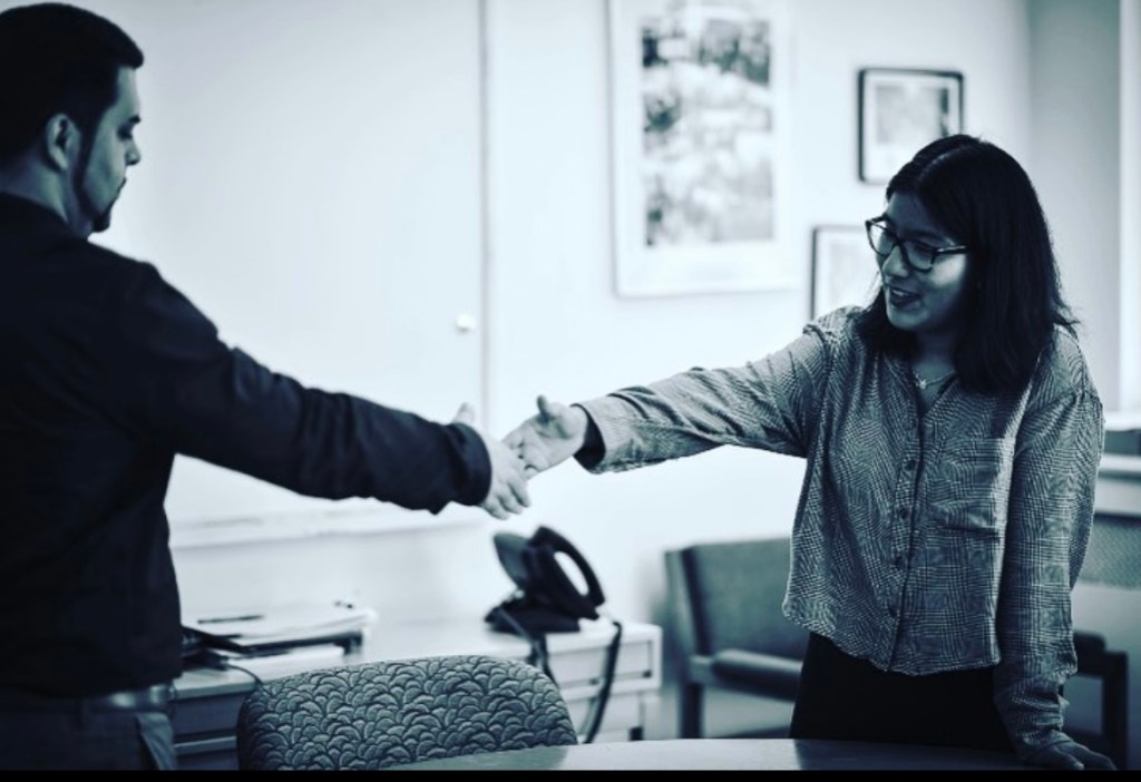 The fourth picture is a black & white photo of Karla shaking hands with Jonathan Marin, the program director for the Career Discovery Project.