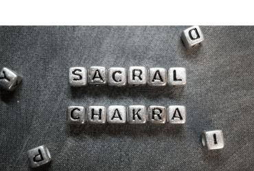 Close up shot of block letters that spell out Sacral Chakra against a dark gray backgound