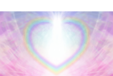 Rainbow heart shape making a border on a radiating delicate pink background with a light burst at the center of the heart shape.