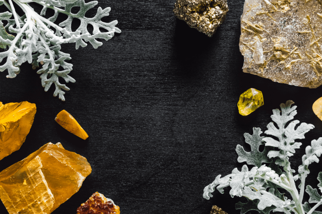 Yellow stones of the solar plexus chakra with Dusty Miller on a black background.