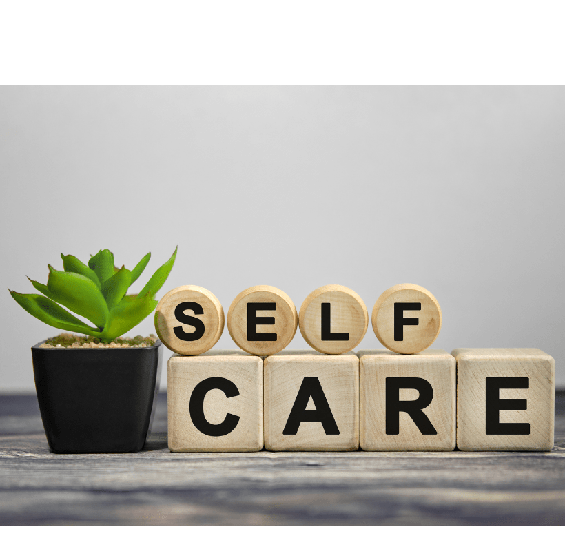 The header is self care text on wooden cubes with a green plant in a black pot on a wood table.