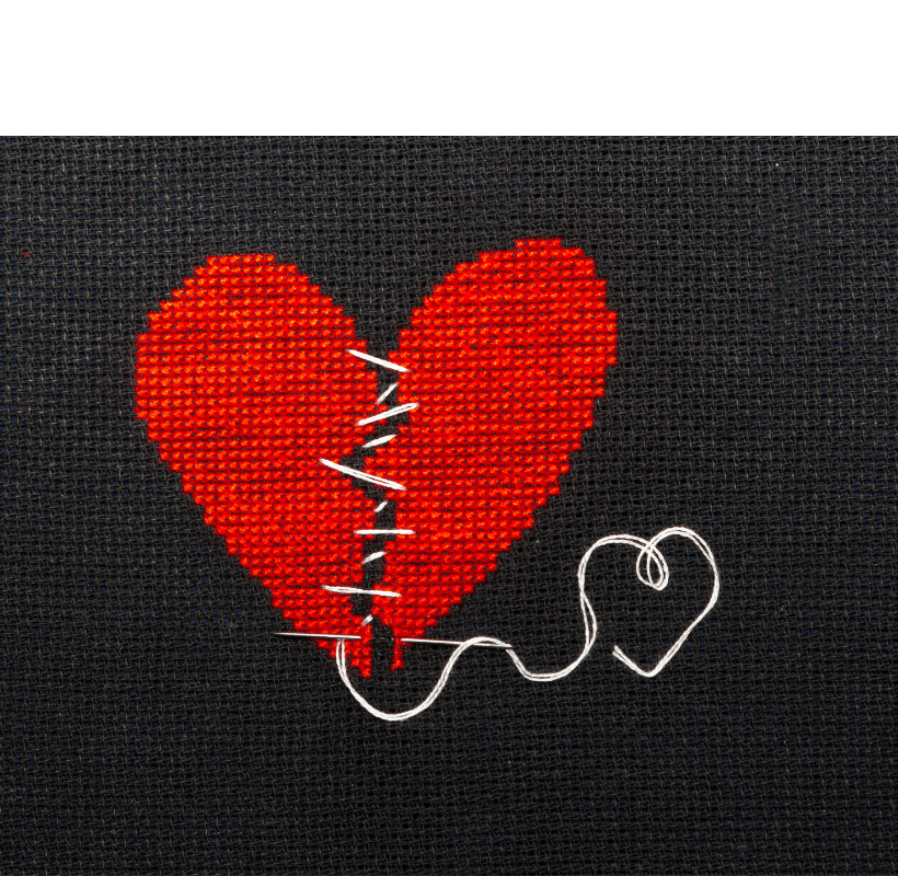 Two halves of a red heart embroidered on black fabric sewn together with white thread.