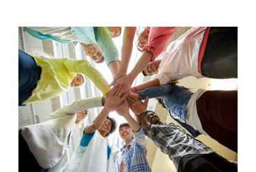 Teamwork concept photo of college students standing in a circle with their hands on top of one another. The shot is looking upward from under their hands.